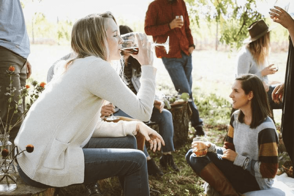 A group of friends shares drinks and chats outside.